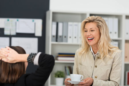 white coffee: Close up Adult Businesswoman, Holding A Cup of Coffee, Laughing while Talking to her Co- Employee Woman at the Office.