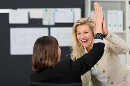five people: Close up Happy White Businesswoman Showing High Five Sign at the Office.