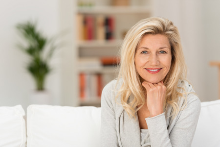 Close-up Pretty volwassen vrouw zittend op een witte sofa met de handen op de kin. Veroverde haar tijdens het kijken naar de camera. Stockfoto