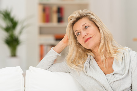 Attractive woman with a wistful expression sitting relaxing on a sofa in the living room looking off pensively to the side Stok Fotoğraf
