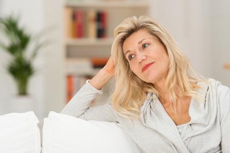 Mujer atractiva con una expresión melancólica Relajación que se sienta en un sofá en la sala de estar mirando fuera ondeante al lado Foto de archivo - 35059033
