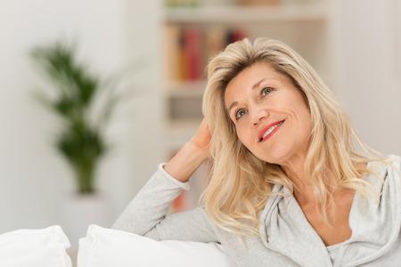 Atractiva mujer sentada soñar despierto en su sala de estar mirando hacia arriba en el aire con una expresión meditativa y sonrisa Foto de archivo - 35059034