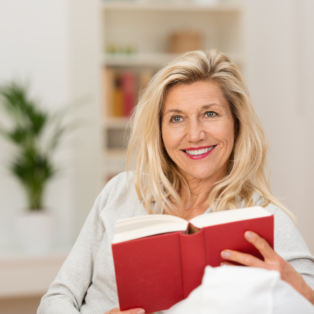 contemplates: Thoughtful attractive middle-aged woman sitting reading a book looking up into the air with a smile as she contemplates what she has just read