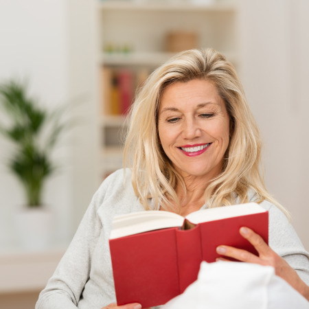 boomer: Attractive blond middle-aged woman enjoying reading a book sitting on the sofa in her living room smiling as she reads Stock Photo