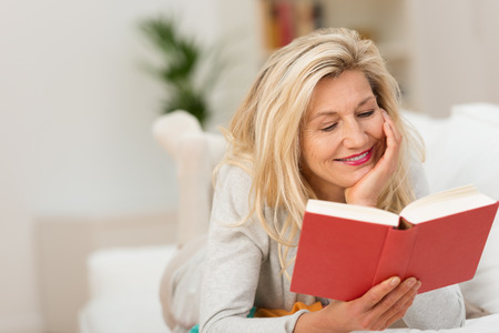 pleasure of reading: Attractive middle-aged blond woman relaxing at home on the sofa reading a book with a smile of pleasure Stock Photo