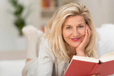 Close up Smiling Adult Woman with Blond Hair Lying on White Sofa with Hand on the Face While Reading a Red Book. Captured Her While Looking at the Camera.