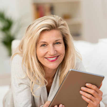 Smiling woman holding a tablet in her hands lying on a sofa in the living room looking at the camera with a wide charming smile photo