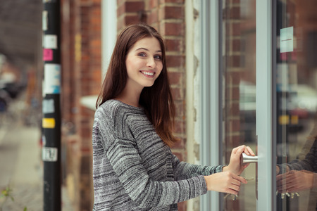 as: Smiling attractive young female student entering a commercial building looking at the camera as she pushes open the glass door