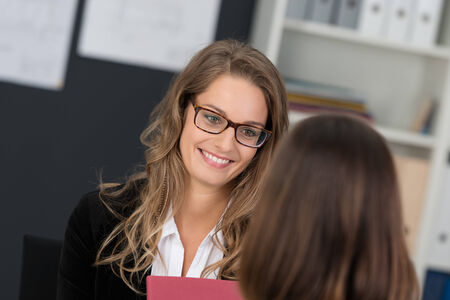 facing away: Attractive businesswoman with a friendly smile wearing glasses having a meeting with a female colleague who is facing away from camera Stock Photo