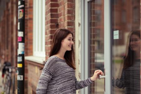Young woman entering an urban building through a large glass door off an urban street Archivio Fotografico
