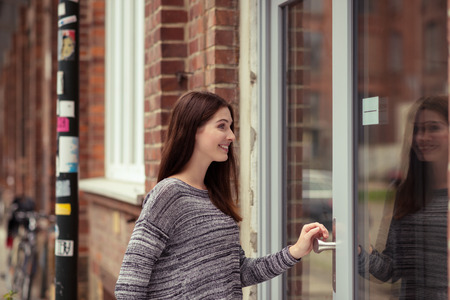 Young woman entering an urban building through a large glass door off an urban street Stock Photo