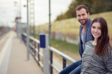 await: Attractive young couple waiting at a railway station standing on the platform smiling at the camera as they await the arrival of the train Stock Photo
