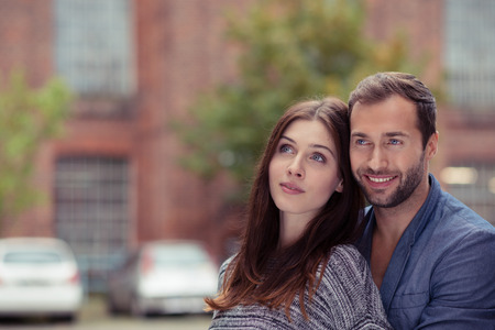 they are watching: Affectionate couple standing close together watching something in the air or daydreaming as they look upwards with a smile, outdoors with copyspace Stock Photo