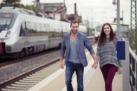 parejas caminando: Pareja joven sonriendo y tomados de la mano caminando por un andén de la estación hacia la cámara con un tren se detuvo en la pista opuesta