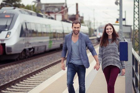 railroad station platform: Young couple smiling and holding hands walking down a station platform towards the camera with a train pulled in on the opposite track