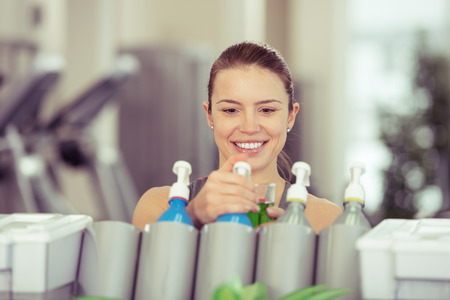 isotonic: Young woman pouring isotonic energy drink from a dispenser in a gym to rehydrate after a workout in a health and fitness concept Stock Photo