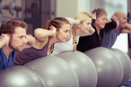 exercises: Group of diverse people in a receding line doing pilates in a gym balancing over the gym balls with their hands laocked behind their necks toning their muscles Stock Photo
