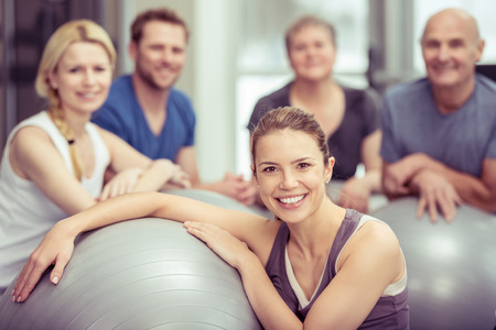 medium body: Group of diverse people in a pilates class at a gym posing with their gym balls looking at the camera with focus to an attractive young woman in the foreground