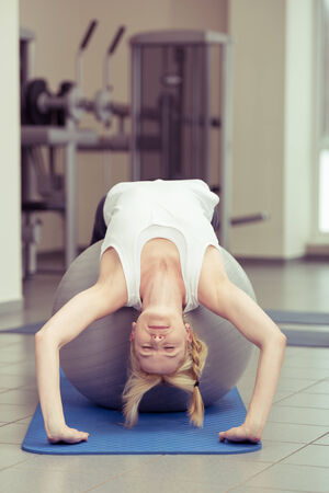 bending over: Supple young woman doing pilates exercise bending backwards over a gym ball strengthening and toning her muscles in a fitness and healthy lifestyle concept