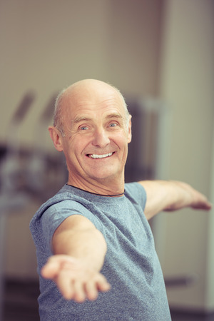 physical activity: Happy attractive elderly man working out doing aerobic exercises standing with his arms raised giving the camera a friendly smile Stock Photo