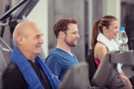 man working out: Group of diverse people in a gym working out together on the equipment with an elderly man and young woman with focus to the smiling face of a young man in the centre, in a health and fitness concept