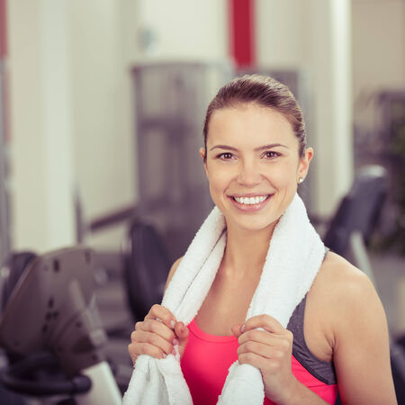 fitness center: Happy vivacious attractive young woman in a gym standing with a towel around her shoulders smiling at the camera, head and shoulders Stock Photo