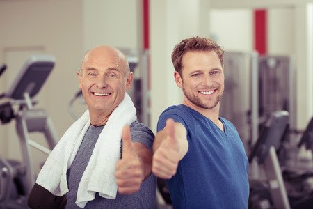 alright: Two happy men, one elderly and one young, in a gym giving a thumbs up of approval and success in a healthy lifestyle and fitness concept Stock Photo