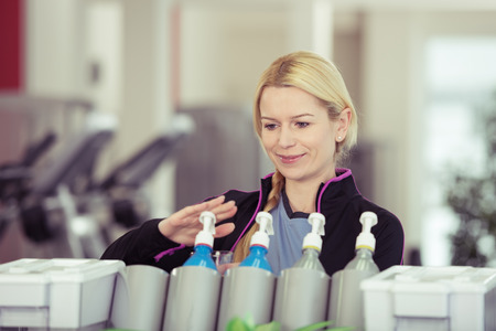 isotonic: Attractive young blond woman dispensing isotonic high energy juice in a gym from a vending machine Stock Photo