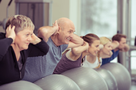 exercises: Happy elderly couple exercising in a pilates class at the gym with three other younger people toning and strengthening their muscles using gym balls, focus to the senior man and woman