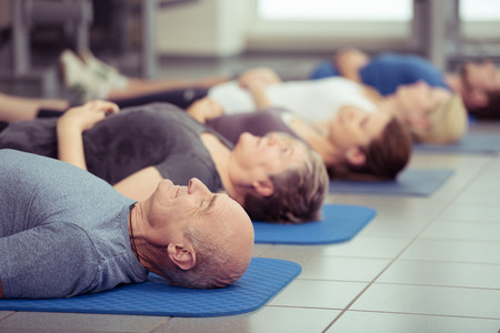 old lady: Senior couple participating in aerobics class at the gym with diverse people lying in a receding row on mats, focus to the couple in the foreground, healthy lifestyle concept