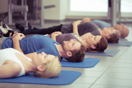 Young couple doing aerobics in a gym with a group of diverse people in a receding row, focus to the young man and woman in the foreground, health and fitness concept