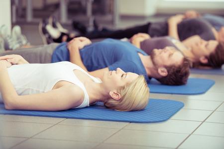 curso de capacitacion: Joven mujer que trabaja en una clase de gimnasio haciendo ejercicios aeróbicos de respiración acostado en una colchoneta, de cerca parte superior del cuerpo en un concepto de salud y fitness