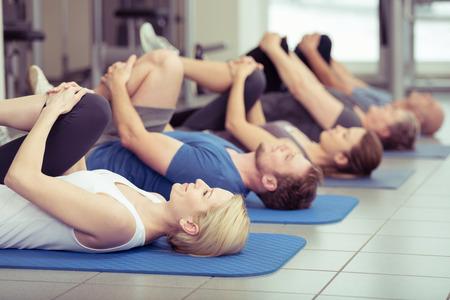 gimnasio: Grupo diverso de los jóvenes y de más edad que ejercen en el gimnasio haciendo pierna flexiona ya que se encuentran en sus espaldas sobre sus esteras en una fila en retroceso, se centran a una joven y atractiva chica rubia en el primer plano