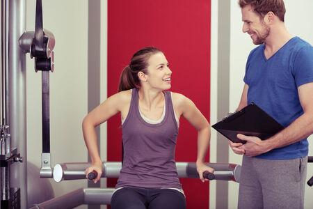 aide � la personne: Jeune femme travaillant avec son entra�neur personnel sur les �quipements dans la salle de gym de pause d'avoir une discussion avec lui au sujet de son progr�s Banque d'images