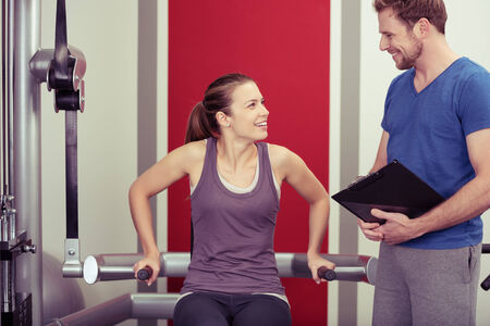 personal: Young woman working out with her personal trainer on equipment in the gym pausing to have a discussion with him concerning her progress