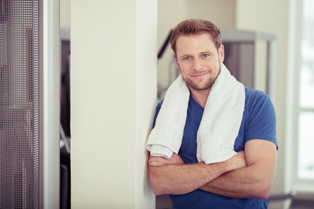 towel: Confident friendly attractive young man at a gym posing with a towel round his neck and folded arms smiling at the camera