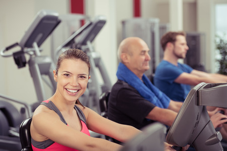 cardio fitness: Smiling Woman Looking at Camera Using Recumbent Exercise Bike in Busy Gym Stock Photo