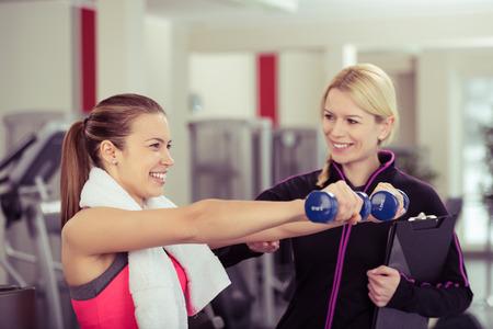 física: Mujer que usa pesos de la mano que sonríe mientras Entrenador Personal Supervisa Su Progreso