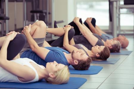ejercicio aer�bico: Grupo diverso de personas en una clase de gimnasia que mienten en una fila que retrocede sobre esteras haciendo pierna se flexiona en un concepto de salud y fitness