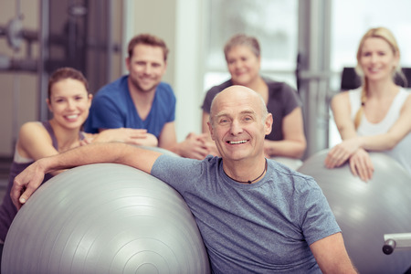 aerobics: Smiling happy fit senior man in a gym class with a group of diverse people leaning on a pilates ball looking at the camera in a healthy lifestyle concept