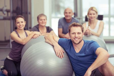 Glimlachend knappe jonge man in pilates klasse in de sportschool zit leunend op zijn sportschool bal met de rest van de diverse groep verzamelde achter hem