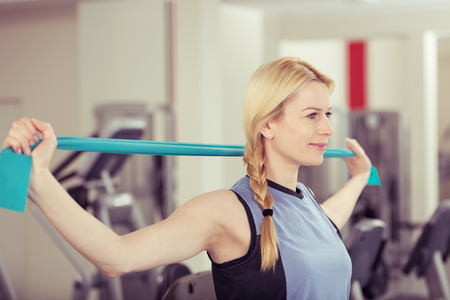 elastic: Attractive young blond woman exercising in a gym stretching and toning her muscles in a health and fitness concept Stock Photo