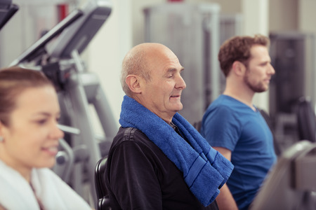 group fitness: Senior man working out in a gym flanked by a young man and woman with focus to the older man in a health and fitness concept Stock Photo