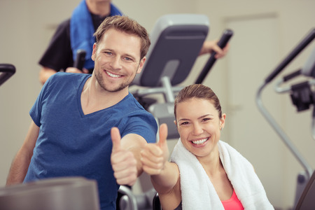 thumbs: Healthy enthusiastic young couple in a gym giving a thumbs up of approval while smiling at the camera in a health and fitness concept