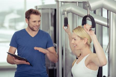 aide � la personne: Bonne sant� Pretty Woman physique � la salle de gym avec son instructeur Jeune Homme Gym Banque d'images