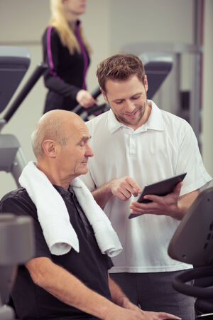 physical training: Personal trainer working with a senior man in a gym showing him his records and progress in a health and fitness concept