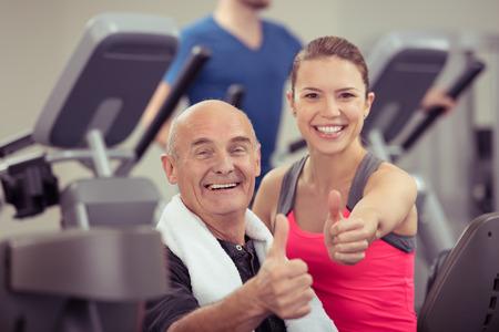 幸せな健康な年配の男性人と笑顔でカメラを見てカメラの成功のジェスチャー親指を与えてジムで若い女性 写真素材