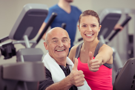 fitness trainer: Happy healthy senior man and young woman in a gym giving the camera a thumbs up gesture of success as they look at the camera with beaming smiles