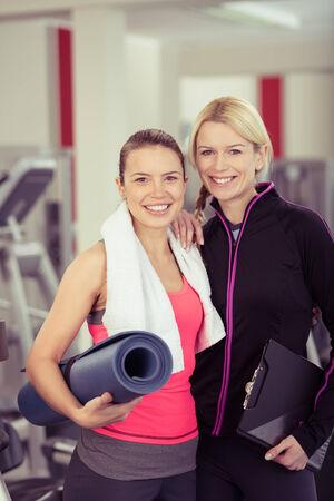 aide � la personne: Close up Fit jeune femme avec Mat posant avec son instructeur Femme Gym au Gym Fitness.