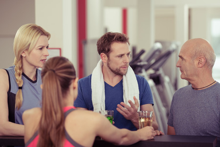 isotonic: Diverse group of young and old people enjoying refreshments at the gym after a physical workout in a health and fitness concept